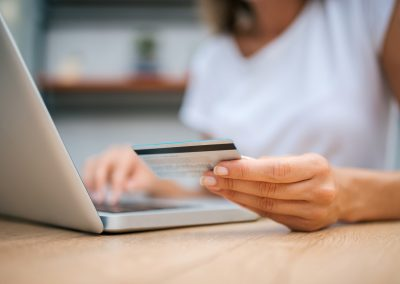 Close-up image of female person using credit card for online shopping.